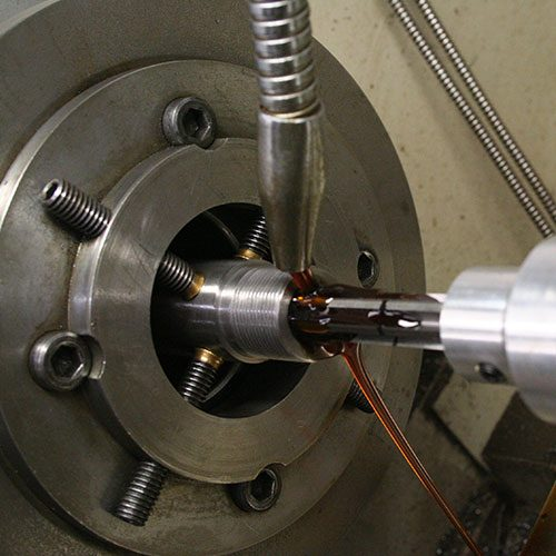 Rifle barrel in a lathe being chambered by a gunsmith.
